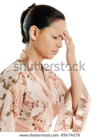Portrait of Asian woman with headache in studio on isolated white background - stock photo