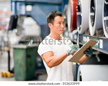 portrait of asian worker in production plant working on the factory floor - stock photo