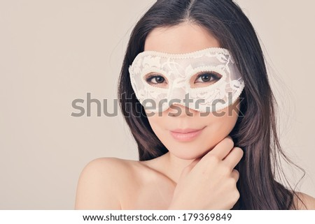Portrait of Asian young beautiful woman in a carnival mask, closeup image in vintage style. - stock photo