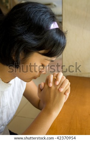 portrait of asian young woman praying in church - stock photo