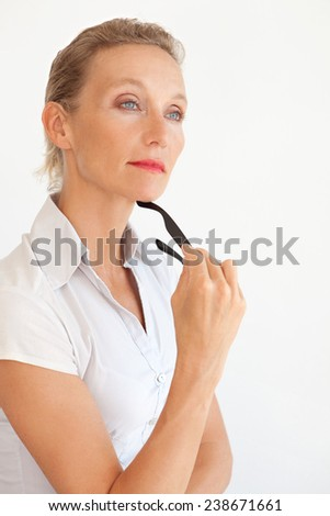 Portrait of aspirational mature office manager sitting and relaxing on her desk at work, confident and strong, holding reading glasses in hand being thoughtful. Professional businesswoman in office. - stock photo