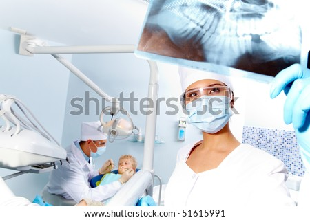 Portrait of assistant looking at patient? x-ray photography during dental examination - stock photo