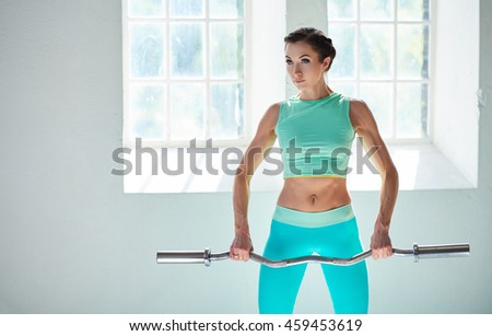 Portrait of athletic female in azure sportswear holding berbell.
