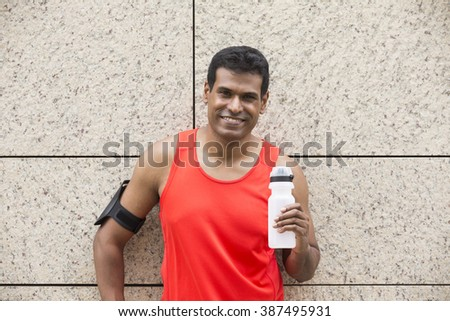 Portrait of athletic Indian man resting after urban run through city streets. Asian male runner taking break standing relaxing. - stock photo