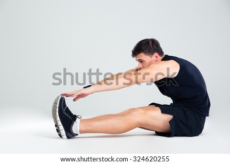 Portrait of athletic man doing stretching exercises isolated on a white background