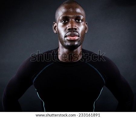 Portrait of athletic man running in black background. - stock photo