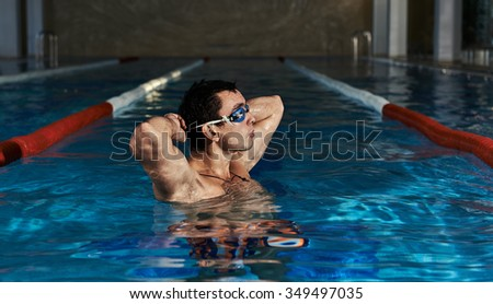 Portrait of athletic swimmer putting on goggles standing in the water. Young Caucasian sportsman in swimming pool.