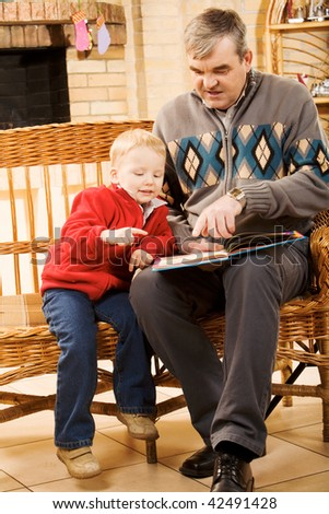 Portrait of attentive boy looking at page of book while reading it with his grandfather - stock photo