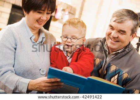 Portrait of attentive boy looking at page of book while reading it with his grandparents - stock photo