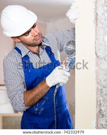 Portrait of attentive repairer man standing with electric saw in uniform indoors