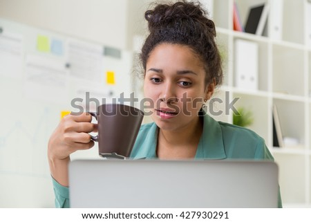 Portrait of attractive african american woman drinking coffee white using laptop in office - stock photo