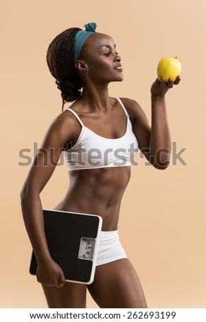 Portrait of attractive african smiling woman eating green apple and holding scales on beige studio background, looking away - stock photo