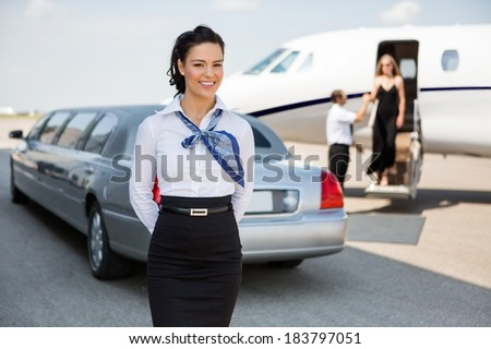 Portrait of attractive airhostess standing against limousine and private jet at airport terminal - stock photo