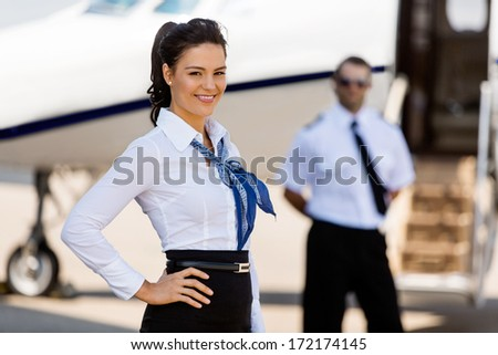 Portrait of attractive airhostess with pilot and private jet in background at terminal - stock photo