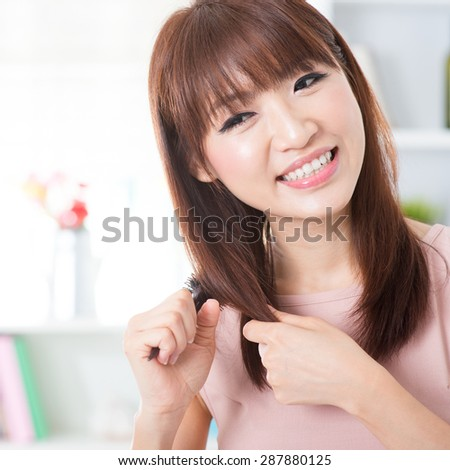 Portrait of attractive Asian girl combing hair in the morning. Young woman indoors living lifestyle at home. - stock photo