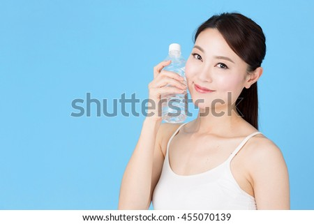 portrait of attractive asian woman isolated on blue background