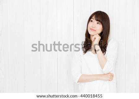 portrait of attractive asian woman isolated on wood background - stock photo