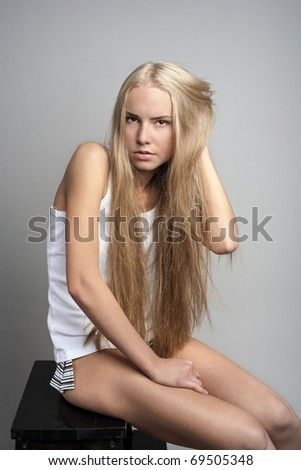 portrait of attractive beautiful young girl posing on grey background