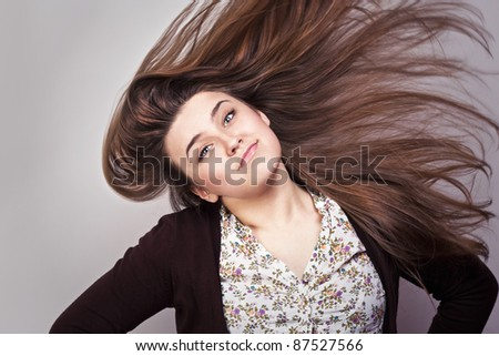 portrait of attractive beautiful young girl posing on grey background - stock photo