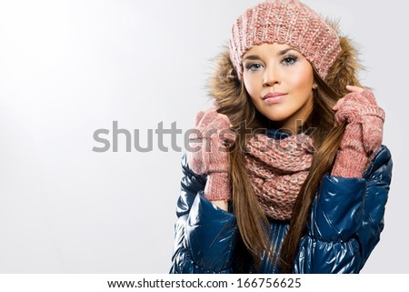 Portrait of attractive beautiful young woman wearing gloves, scarf and winter cap, white background - stock photo