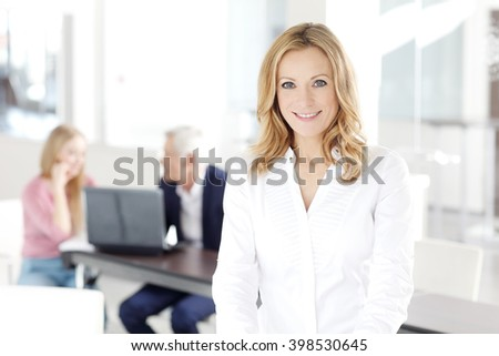 Portrait of attractive blond businesswoman standing at office while her colleagues working at background.