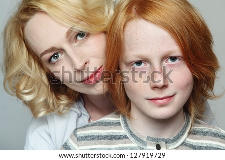 Portrait of attractive blond mother hugging her son teenager, focus on boy - stock photo