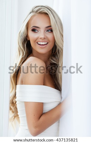 Portrait of attractive blond smiling woman in white - stock photo