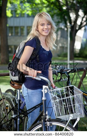 Portrait of attractive blonde female student standing with her bike - stock photo