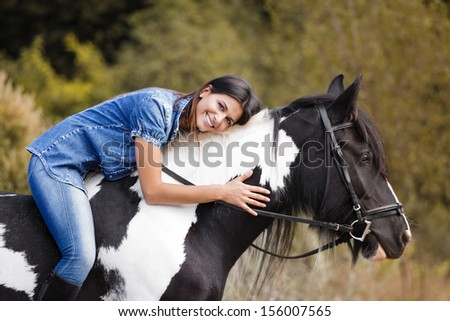portrait of attractive brunette female rider embracing her horse and smiling - stock photo