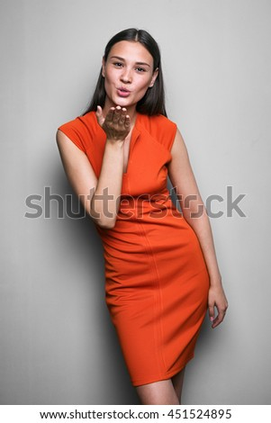 Portrait of attractive brunette girl in red dress blowing air kiss at camera.Studio shot. - stock photo