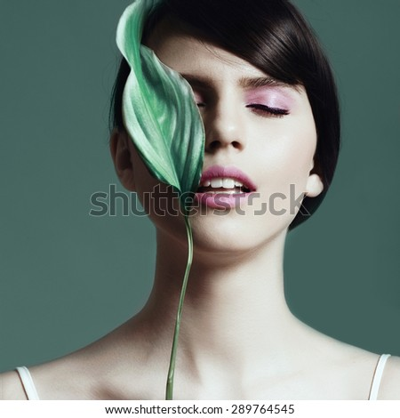 Portrait of attractive brunette girl with a green leaf in the studio, the concept of beauty and health - stock photo