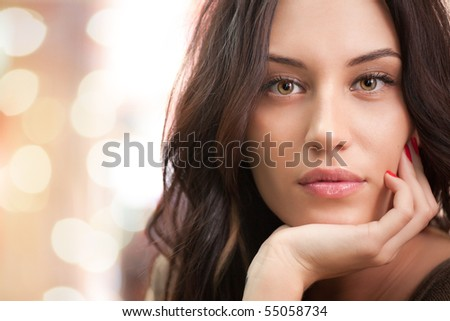Portrait of attractive brunette girl with bokeh lights on background - stock photo