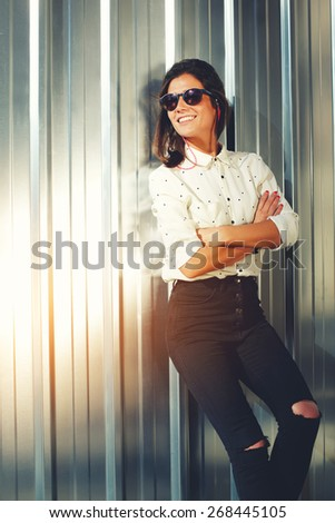 Portrait of attractive brunette hipster woman posing on shiny wall background in sunglasses, smiling fashionable model standing on silver background with crosse arms - stock photo