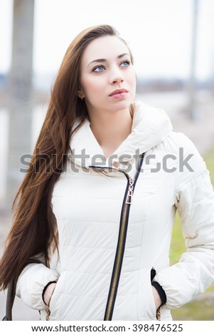 Portrait of attractive brunette in white jacket posing outdoors - stock photo