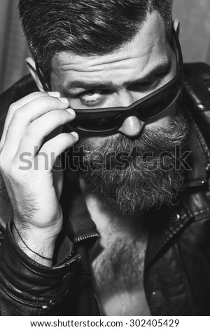 Portrait of attractive brutal unshaved male biker with long beard and moustache in leather jacket and sunglasses looking forward black and white, vertical picture - stock photo