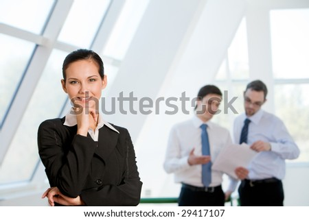 Portrait of attractive business lady looking at camera with smile with men discussing ideas at background