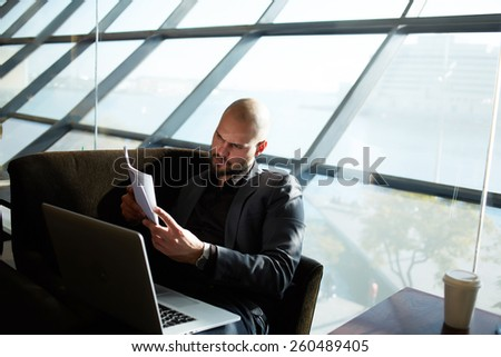 Portrait of attractive business man reviewing a contract while sitting at beautiful office hall with open laptop computer, managing director examining paperwork during his coffee time - stock photo