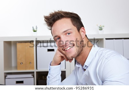 Portrait of attractive business man smiling in office - stock photo