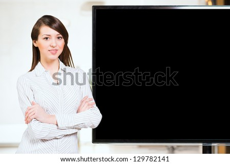 Portrait of attractive business woman crossed her arms, near a monitor with space for text