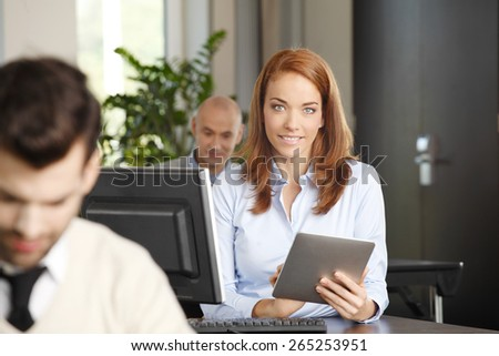 Portrait of attractive business woman sitting at desk in front of computer and analyzing financial data on digital tablet. Business team working at background.