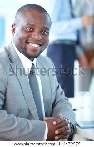 Portrait of attractive businessman looking at camera in working environment - stock photo