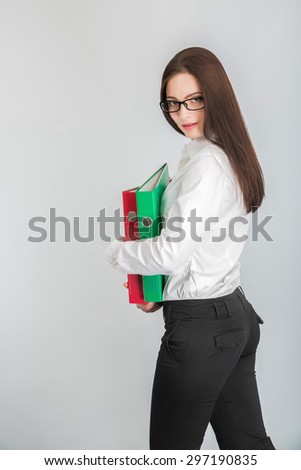 Portrait of attractive businesswoman in glasses holding red and green folders  - stock photo