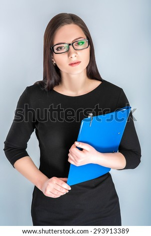 Portrait of attractive businesswoman in glasses with blue folder on blue background - stock photo