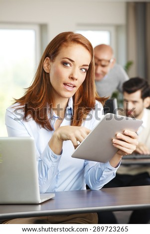 Portrait of attractive businesswoman sitting at office in front of laptop and holding hands digital tablet. Mature woman touching the screen while using private banking online.  - stock photo