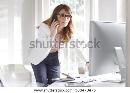 Portrait of attractive businesswoman talking on mobile phone while sitting at her workplace and working on computer. - stock photo