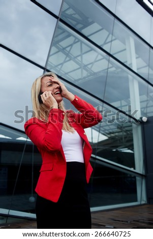 Portrait of attractive businesswoman throwing her head back with one hand on her face in laughter having conversation on cell phone, woman laughing during talking to friend on smart phone - stock photo