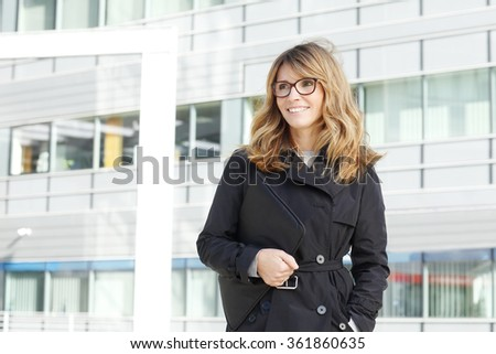 Portrait of attractive businesswoman walking on the street after business meeting.  - stock photo