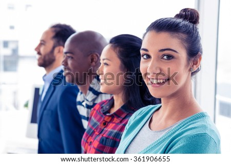 Portrait of attractive businesswoman with colleagues standing in creative office - stock photo