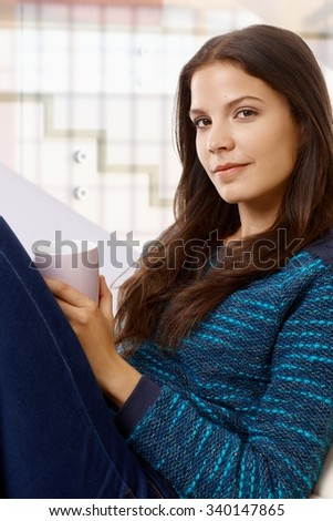 Portrait of attractive casual caucasian attractive woman sitting with cup in hand indoors. Smiling, looking at camera. - stock photo