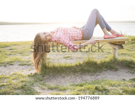 Portrait of Attractive caucasian female with long  brown hair lie on the bench at the beach against green fresh green grass , sea and sunset sky background . - stock photo